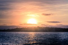 Golden sunset over calm bay waters with hilly coast at the distance. royalty free stock photo