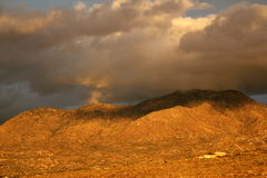 Golden sunset over Catalina mountains in tucson, arizona. Big sky at sunset full of golden storm clouds over the catalina mountains at  in Tucson, Arizona Stock Images