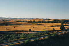 Golden sunset over farm field with hay bales Royalty Free Stock Images