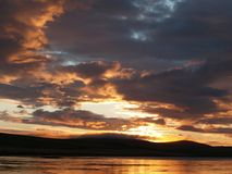 Golden sunset over lake. Scenic view of golden sunset and dark cloudscape over lake with hills in background, Orkney Islands, Scotland royalty free stock image