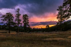 Golden Sunset over the Mountain. An orange, purple and blue Sunset over the evergreen trees in the Chuska Mountains, which is on the Navajo Indian Reservation in Royalty Free Stock Photos