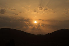Golden sunset over mountains. Beautiful sunset over mountains silhouette. Sunrays through the clouds Stock Images