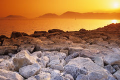 Golden sunset over rocks. Scenic view of golden sunset over rocks on picturesque coastline, Lerici, Italy Royalty Free Stock Image