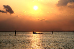 Golden sunset over sea. Scenic view of golden sunset over sea with silhouetted boat in foreground Royalty Free Stock Photos