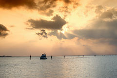 Golden sunset over sea. Golden sunset and cloudscape over sea with boat silhouetted in foreground Royalty Free Stock Photography