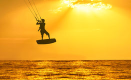 Golden sunset over the sea with the men kiting silhouette Royalty Free Stock Photos