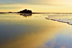 Golden Sunset on Pacific Coast. View on seastacks on Pacific coast and wet sand opened by low tide lit with golden sun stock photos