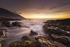 Golden sunset at pacific ocean with waves on rocky shore Royalty Free Stock Image