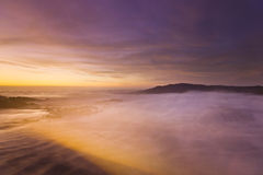 Golden sunset at pacific ocean with waves on rocky shore Royalty Free Stock Photo