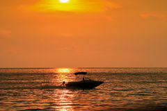 Golden sunset photo with a silhouette of a speed boat Stock Photos