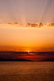 Golden sunset with rays above clouds, sun covered by cloud Stock Images