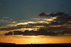 Golden Sunset. Sepia-colored centered sunset and dark clouds Royalty Free Stock Photos