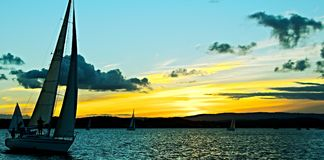 Golden Sunset Silhoette Sails. Sailing yacht in silhouette with golden sunset and water reflections Royalty Free Stock Images