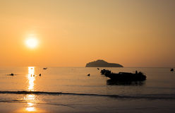 Golden sunset silhouette with boats and people Stock Photography