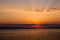 Golden sunset with sun covered by clouds, rays above clouds Royalty Free Stock Photo