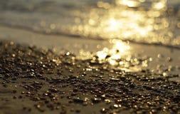 Golden sunset on Baltic sea coast, DOF. Golden sunset in waves on Baltic sea coast with wet stones in foreground, DOF Stock Photo