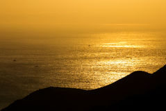Golden sunshine on the sea. Where fish boats is going through. The sea with light fog in distant Royalty Free Stock Photography