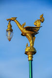 A Golden Swan Lamppost. A golden mythical swan lamppost against a clear blue sky stock image