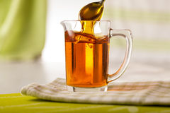 Golden Syrup. In jug with spoon pulling syrup out about to serve Stock Image