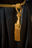 Golden tassel on black curtain Stock Photography