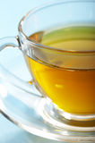 Golden tea. Fragment glass cup of tea over blue Stock Images