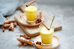 Golden tea with almond milk, turmeric, cinnamon, honey and ginger. Healthy detox morning beverage with spices on light backround. Golden latte with almond milk stock image