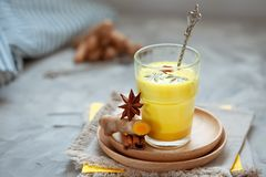 Golden tea with almond milk, turmeric, cinnamon, honey and ginger. Healthy detox morning beverage with spices on light backround. Golden latte with almond milk stock photo