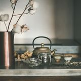 Golden teapot and cups on concrete counter, square crop royalty free stock image