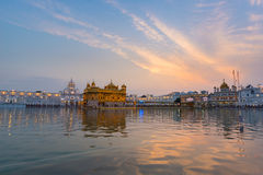 The Golden Temple at Amritsar, Punjab, India, the most sacred icon and worship place of Sikh religion. Sunset light reflected on l. Ake Stock Photos