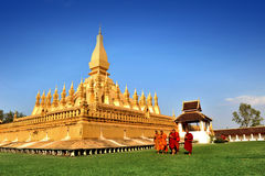 Vientiane, Laos - January 19, 2012:  Group of Buddhist monks walking around That Luang Stupa, landmark of Vientiane, Lao PDR Royalty Free Stock Images