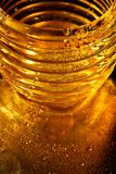 Golden texture with water drops.Thirst and its quenching. Drops of honey on the glass Royalty Free Stock Image