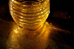 Golden texture with water drops.Thirst and its quenching. Drops of honey on the glass Royalty Free Stock Photos