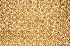 Golden textured oilcloth or leather. Golden close-up textured oilcloth or leather for background Stock Photos