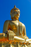 Golden Thailand Buddha in Hinayana tradition in pure blue sky Royalty Free Stock Photos