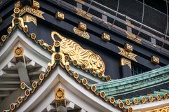 Golden Tiger Ornaments at Osaka Castle in Japan. The main tower of Osaka Castle`s exterior is covered in gold leaf ornaments designed to impress and demoralize stock images