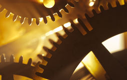 Golden Time. Detail shot of inside of old antique clock showing gears with dramatic lighting Royalty Free Stock Photos