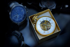Golden times. Golden pocket retro watch among modern watches Royalty Free Stock Photo