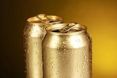 Golden tin cans on yellow Stock Photos