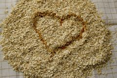Toasted Oat Heart Background. Golden toasted oat heart surrounded by oatmeal. Background. Horizontal Stock Photography