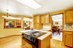 Golden tones kitchen interior with island and skylight Royalty Free Stock Photo