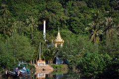 Golden towers of a buddhist temple peeping in a forest on a Thai island in Asia. Golden towers of a buddhist temple peeping in a forest and color boats on the Stock Photography