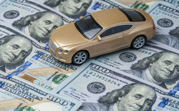 Golden toy car on the background of banknotes. Golden toy car on the background of US dollars. Horizontal view Stock Photo
