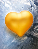 Golden toy heart on frost Stock Image