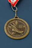 Golden track and field medal. One golden track and field medal running flying shoe portrait (blue background). Nikon raw file was provided Stock Image