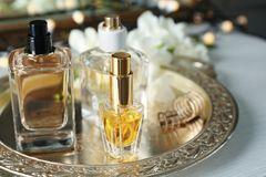 Golden tray with perfume bottles. On white table stock images