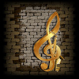 Golden treble clef on a old brick wall Royalty Free Stock Images