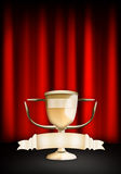 Golden Trophy. On stage with red curtains Royalty Free Stock Photos