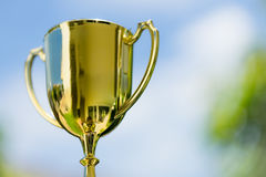 Golden trophy with blue sky background with copy space as winner. Reward or reward concept Stock Photo