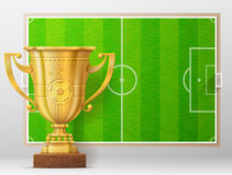 Golden trophy cup against soccer pitch Stock Photo