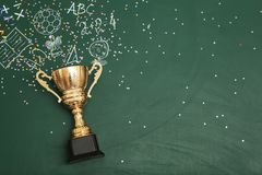Golden trophy cup and chalk drawings on color background, top view. With space for text royalty free stock photography